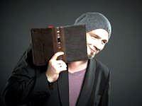 Mann mit Mütze schaut hinter Buch hervor