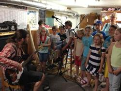 erwachsener Gitarrespiele und singende Kinder