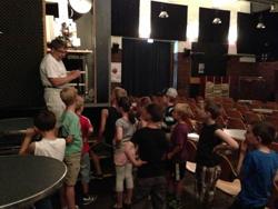 Filmvorführer erklärt Kindern, wie ein Kinofilm abegespielt wird