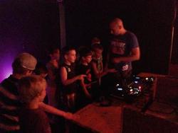 DJ führt Kinder durch Discothek