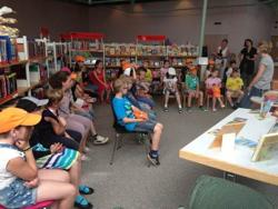 sitzende Kinder in der Stadtbücherei sprechen mit der Büchereileiterin