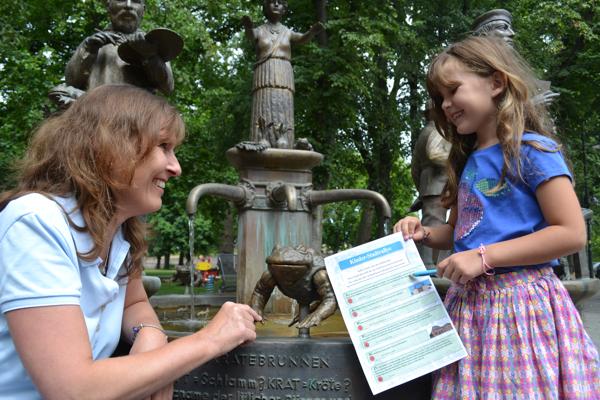 Gasteführerin und Kind vor dem Muttkrate-Brunnen (Foto: Stadt Jülich)