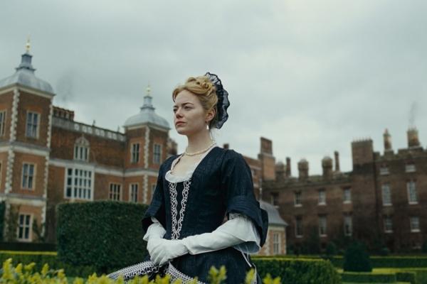 Bild: Eine Frau in historischem Kostüm im Garten vor einem Schloss