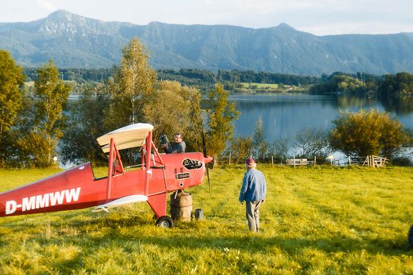 Bild: Ein rotes Propeller-Flugzeug steht auf einer Wiese und wird von einem Mann betankt.