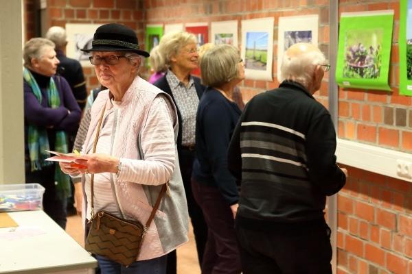 Bild: Mehrere Seniorinnen und Senioren sehen sich die Beiträge an.