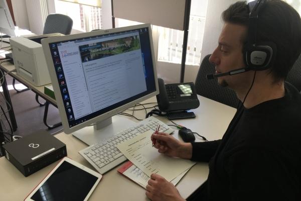 Bild: Ein Mitarbeiter der Hotline vor einem Bildschirm