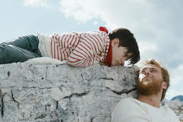 Bild: Der achtjährige Tristan (liegt auf einem Felsen), Aaron (Freund der Mutter) lehnt an dem Felsen. Die beiden schauen sich an.