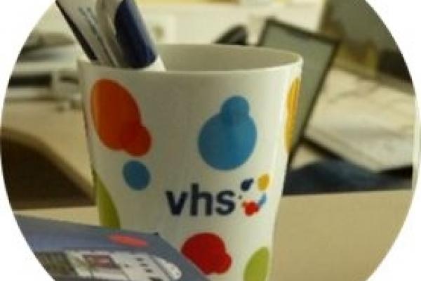 Bild: Eine Tasse mit der Aufschrift VHS und einigen Stiften