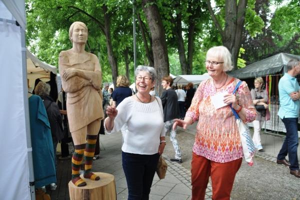 Bild: Kunsthandwerkerinnenmarkt - Holzskulptur und Besucherinnen