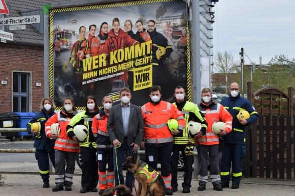 Bild: Vertrerer der verschiedenen HIlfs- und Rettungsdienst vor einem großen Plakat mit der Aufschrfit: Wer kommt, wenn nichts mehr geht? Die Katastrophenschützer*innen. Wenn nicht WIR, wer dann?