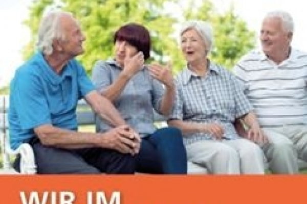 Bild: Seniorinnen und Senioren sitzen miteinander redend auf einer Bank.