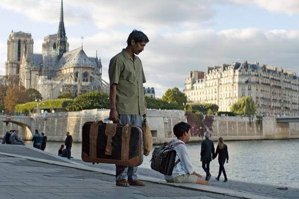 Bild: Fahim sitzt auf einer Treppe mit Blick aufs Wasser. Sein Vater steht mit einem Koffer hinter ihm.