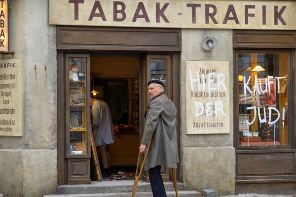 Bild: Ein alter Mann mit Krücken steht vor einem Laden.