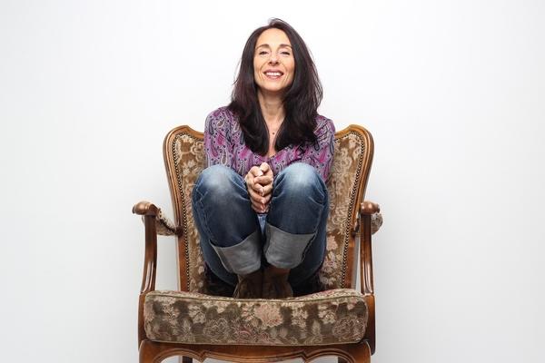 Bild: Antonella Simonetti sitzt mit angezogenen Beinen auf einem Sessel