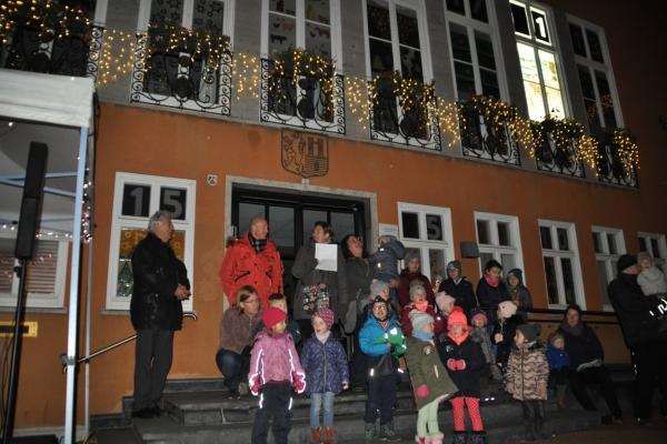 Bild: Gemeinsam stimmten sie sich und die Passanten auf den Advent und die Eröffnung des Rathauskalenders ein: Wolfgang Gunia in Vertretung des Bürgermeisters, Ulf Kamburg als Geschäftsführer der Stadtwerke Jülich und die KiTa St. Rochus.