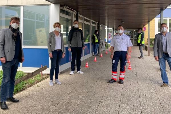 Bild: Bürgermeister Fuchs mit weiteren Personen vor dem Testzentrum Jülich