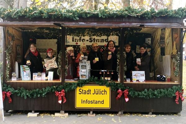 Bild: Das Team der Tourist-Info präsentiert die Souvenirs der Stadt Jülich, die auf dem Weihnachtsmarkt erhältlich sind. Foto: Stadt Jülich/Stein