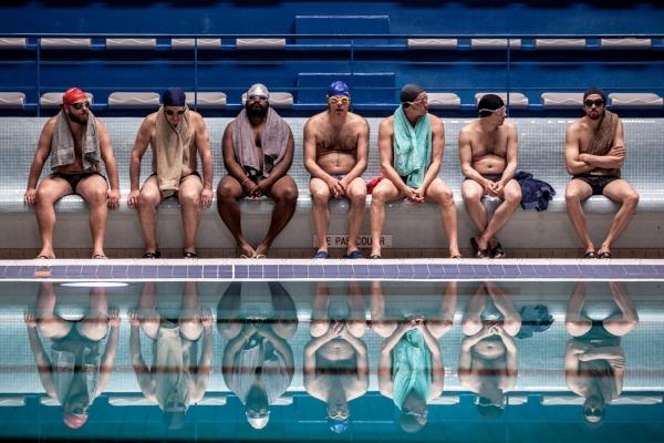 Bild: 7 Männer in Badekleidung sitzen am Ran des Schwimmbeckens auf einer Bank.