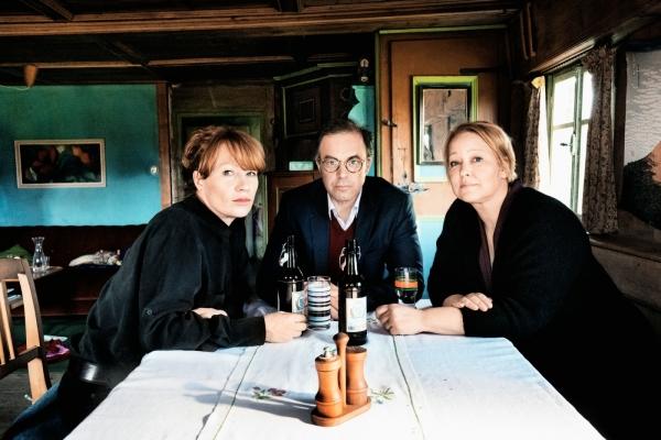 Bild: Die drei Hauptdarsteller sitzen an einem Tisch. Der Mann in der Mitte, die Frauen recht sund links von ihm.