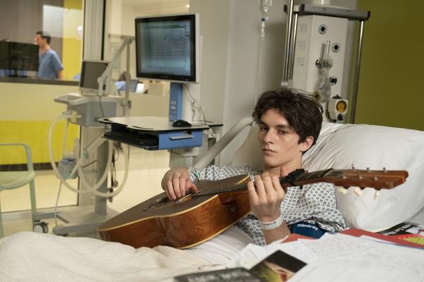 Bild: Der 17-jährige Adam spielt Gitarre im Krankenhausbett