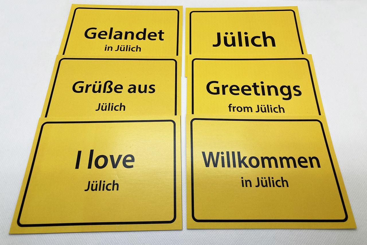 Postkarten mit gelbem Ortsschild, verschiedene schwarze Aufdrucke: Gelandet in…