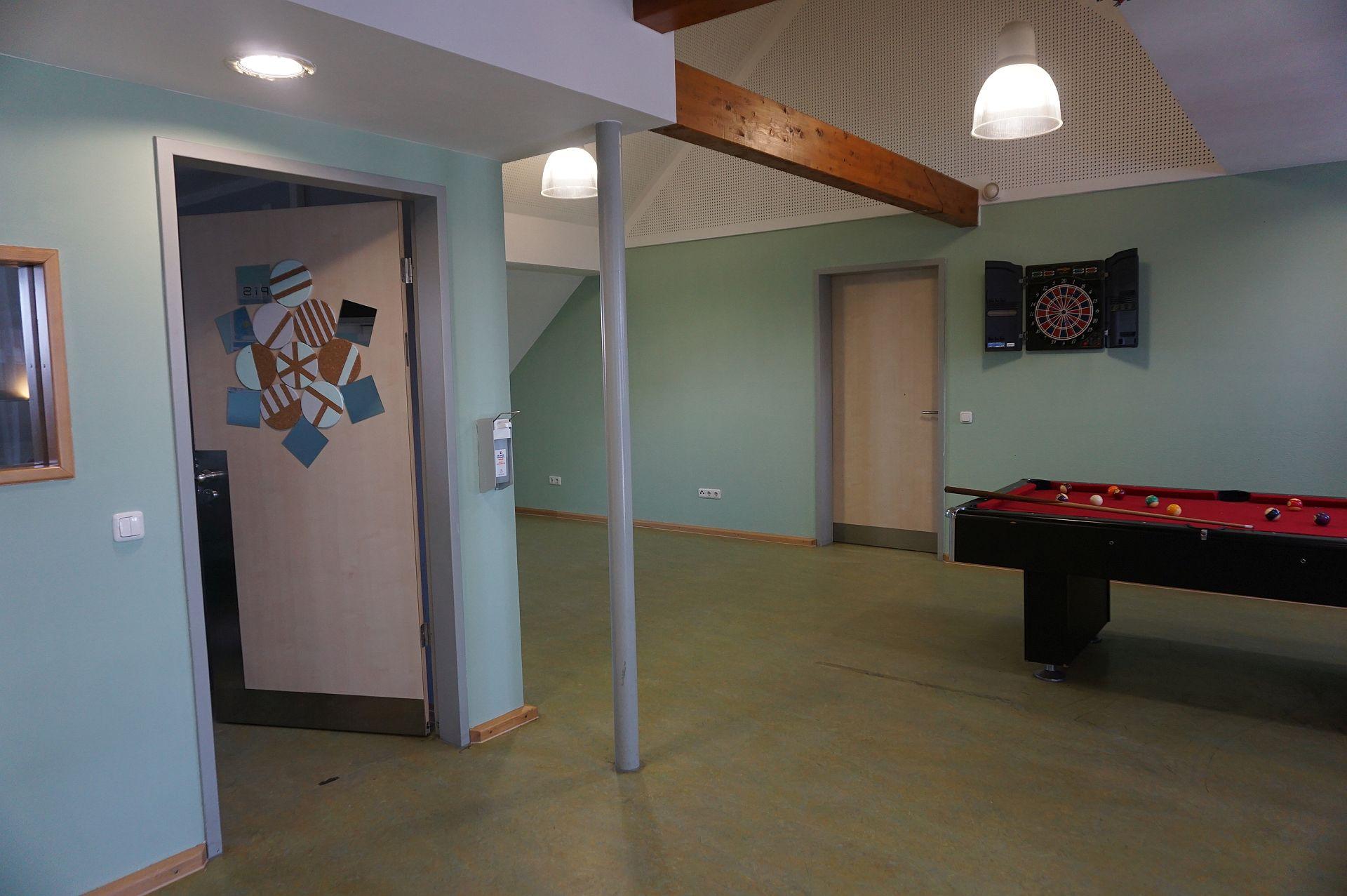 Einblick in einen hellen Raum, holzfarbene Türen, eine Tür beklebt mit bunten Kreisen und Quadraten, an der Wand ein Dartspiel, frei im Raum stehend ein Billardtisch. An der Wand hängend ein Desinfektionsmittelspender.
