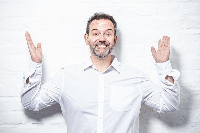 Rene_Steinberg. Bild des Künstlers im weißen Hemd mit erhobenen Händen.