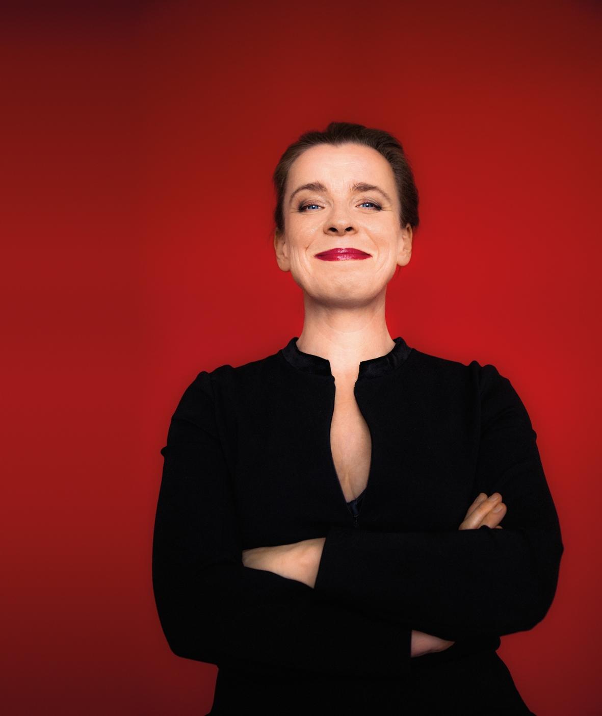 Tina Teubner. Frau im schwarzen Pullover mit verschränkten Armen vor einer roten Wand stehend.